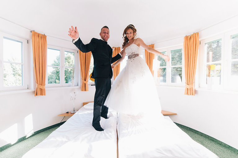 Brautpaar springt im Hotelzimmer auf dem bett herum