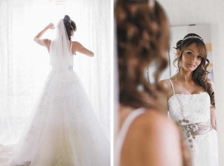 Bild von einer Braut am hellen Fenster und wie sie in den Spiegel schaut