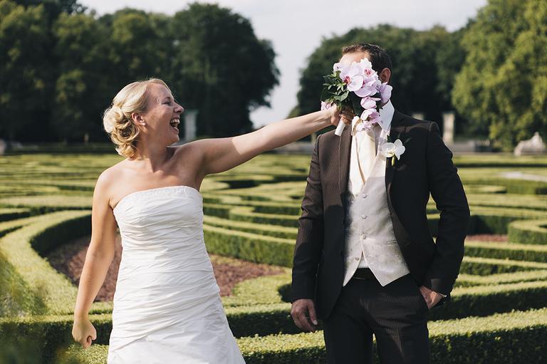 Braut hält Ihrem Bräutigam Ihren Brautstrauß vor das Gesicht im Schloßpark Nordkirchen