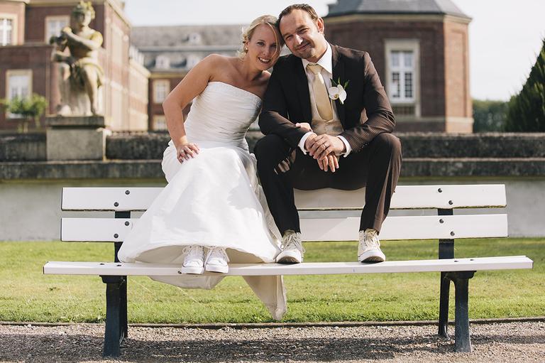 Brautpaar mit Chuks auf einer Bank im Schloßpark Nordkirchen