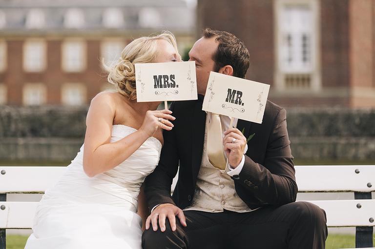 Brautpaar hält sich Schilder vor das Gesicht und küssen sich dahinter