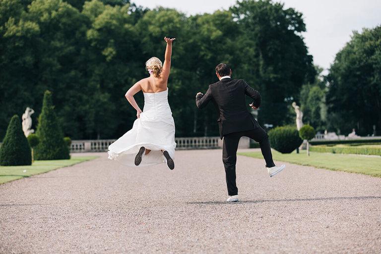 Ausgelassenes Brautpaar in Chucks springend im Schloßpark Nordkirchen