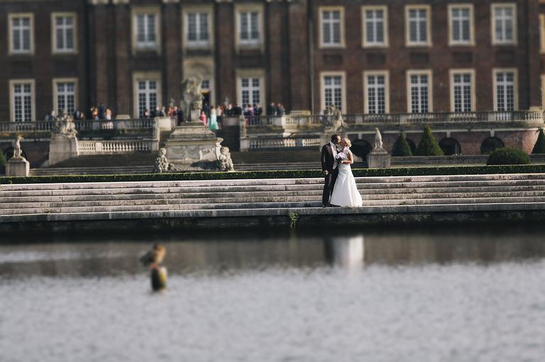 Brautpaar umarmt sich am Wasser und im Hintergrund sieht man das Schloß Nordkirchen