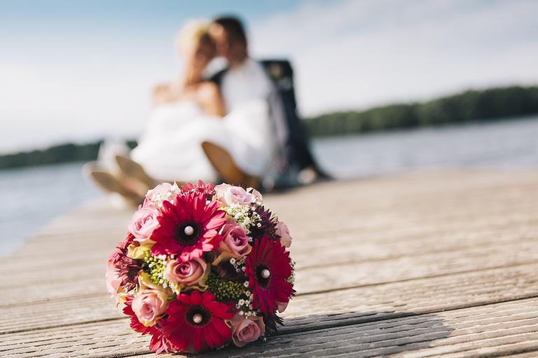 Bild zeigt das Brautpaar auf dem Steg am Drilandsee und im Vordergrund sieht man den Brautstrauß