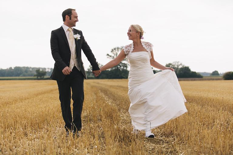 Brautpaar spaziert durch ein Weizenfeld