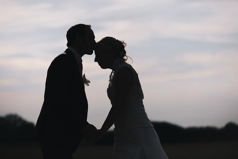 Silhouette von einem Brautpaar wie es sich küsst