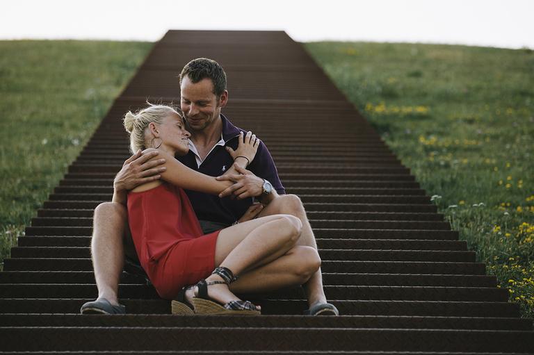 Auf dem Bild liegt sich ein Pärchen im Arm am unteren Ende einer langen Treppe auf einen Hügel