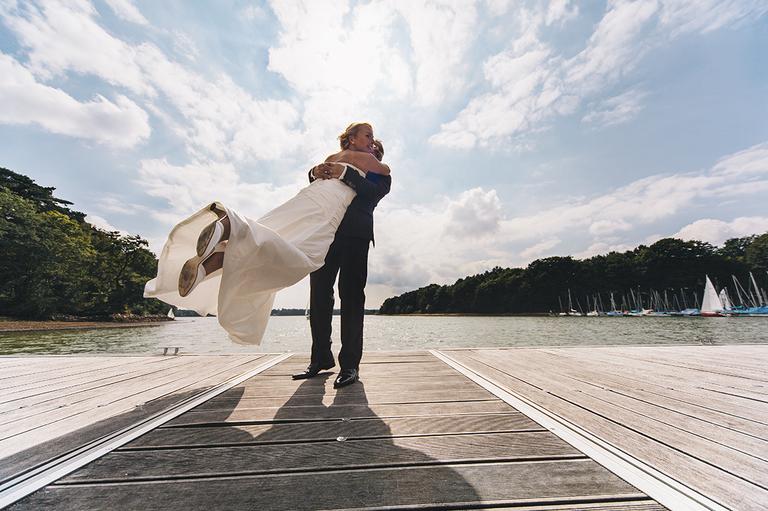 Bräutigam umarmt seine Braut am Halterner Stausee auf einem Steg