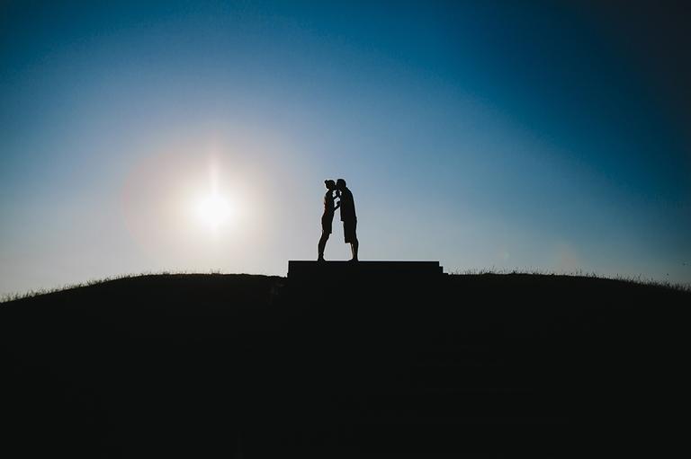Scherenschnitt von einem Paar wie es sich auf einem Hügel küsst