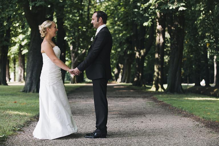 Brautpaar schaut sich an im Schloßgarten Nordkirchen
