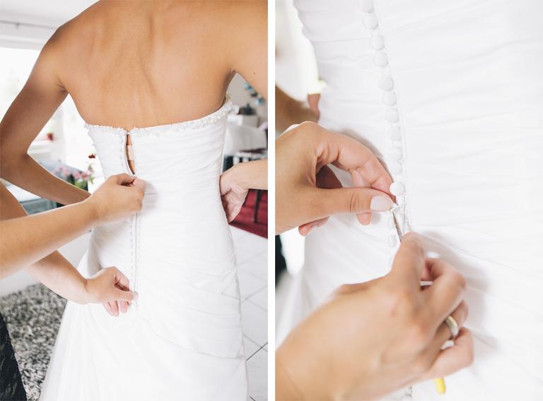Bild von der Braut beim Anziehen des Brautkleides