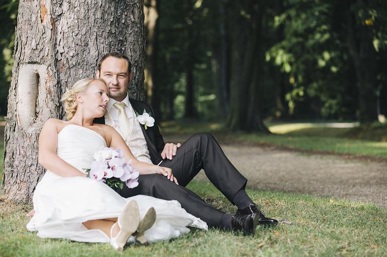 Hochzeitspaar sitzt an einem Baum gelehnt im Schloßpark Nordkirchen