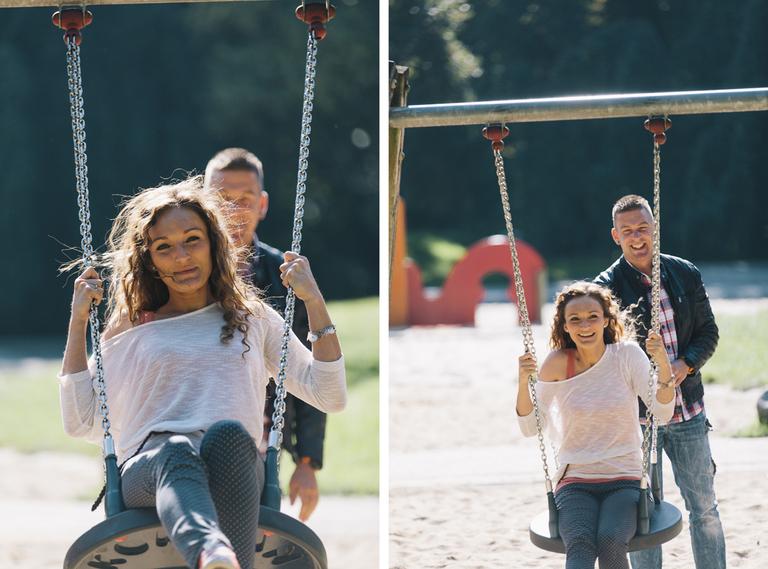 Bild zeigt ein Paar auf einem Spielplatz und Sie sitzt auf einer Schaukel