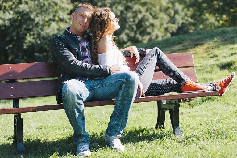 Paar sitzt auf einer Bank während Sie in die Sonne schaut sieht er in die Kamera