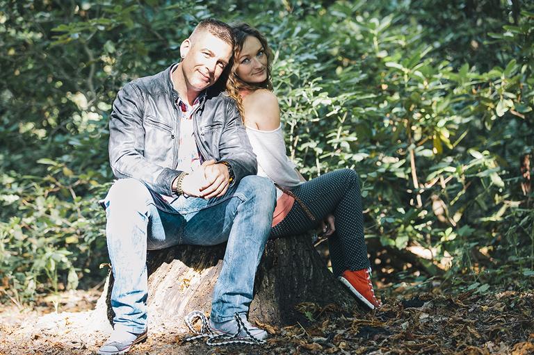 Auf dem Bild sitzt ein Paar auf einem Baumstumpf im Wald