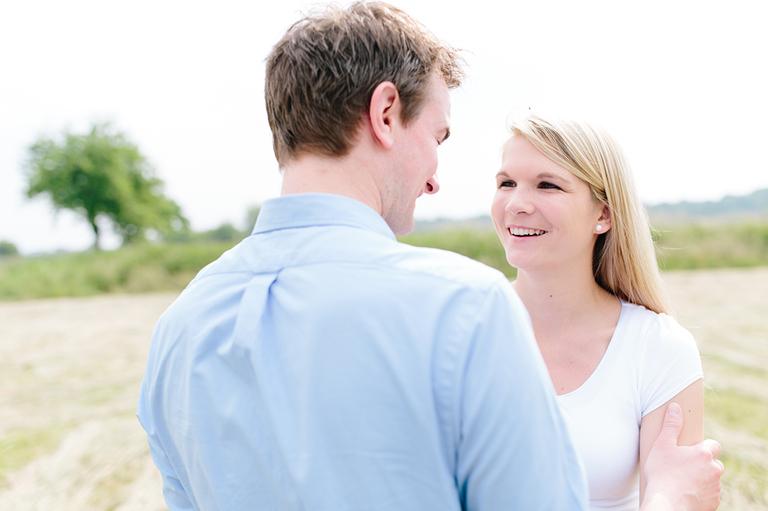 Bild zeigt ein verliebtes Pärchen auf einem Feld und Sie schaut Ihren Freund verliebt an