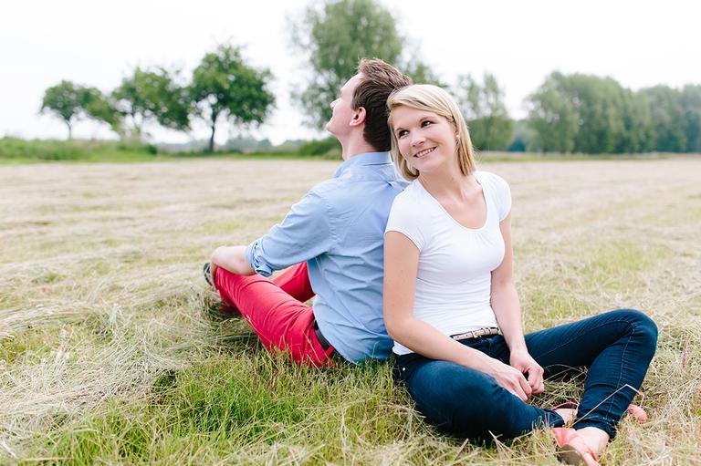 Paar sitzt auf einem Feld und lehnen sich gegenseitig an