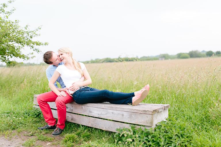 Bild zeigt ein verliebtes Paar auf einer Bank und er umarmt sie