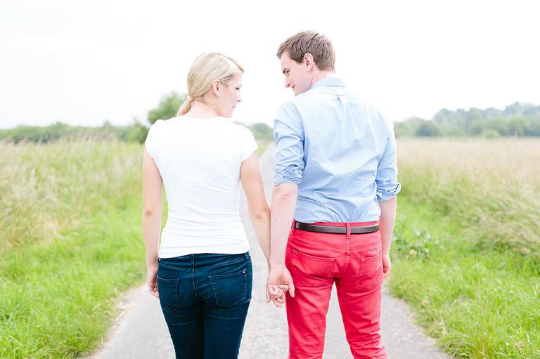 Bild zeigt ein Paar auf einem Weg in den Rieselfeldern von hinten und sie schauen sich verliebt an