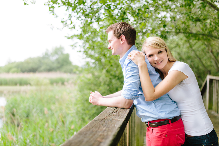Bild zeigt ein Paar auf einer Brücke und sie lehnt sich an seinen starken Rücken und schaut in die Kamera