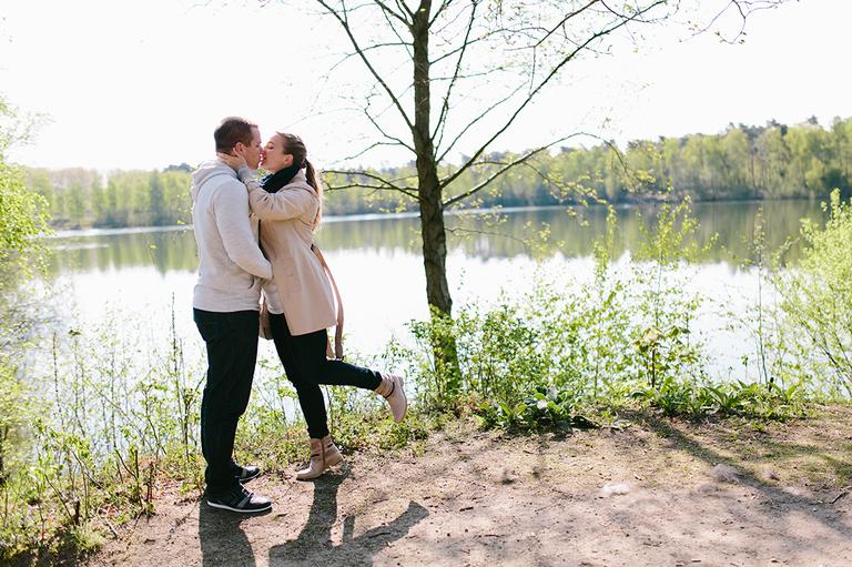 Verliebtes Paar küsst sich am See vor einem Baum