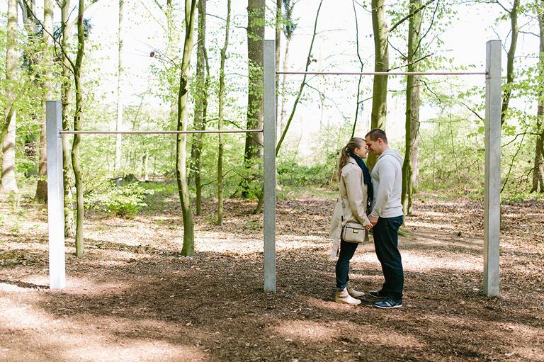 Paar steht unter einer Reckstange im Wald