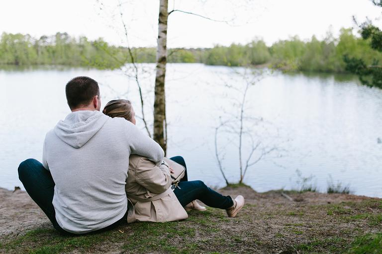 Pärchen liegt an einem See und schaut verträumt auf das Wasser