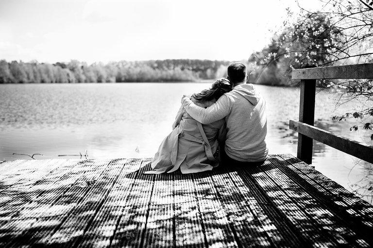 Paar auf einem Steg nimmt sich in den Arm