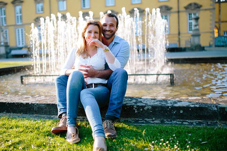 Paar sitzt in Osnabrück am Springbrunnen und schaut verliebt in die Kamera