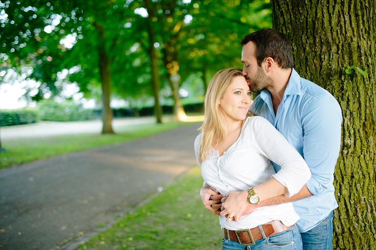 Verliebtes Paar lehnt sich an einen Baum und er küsst sie auf die Stirn