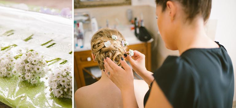 Stylistin steckt der Braut Blumen in das Haar