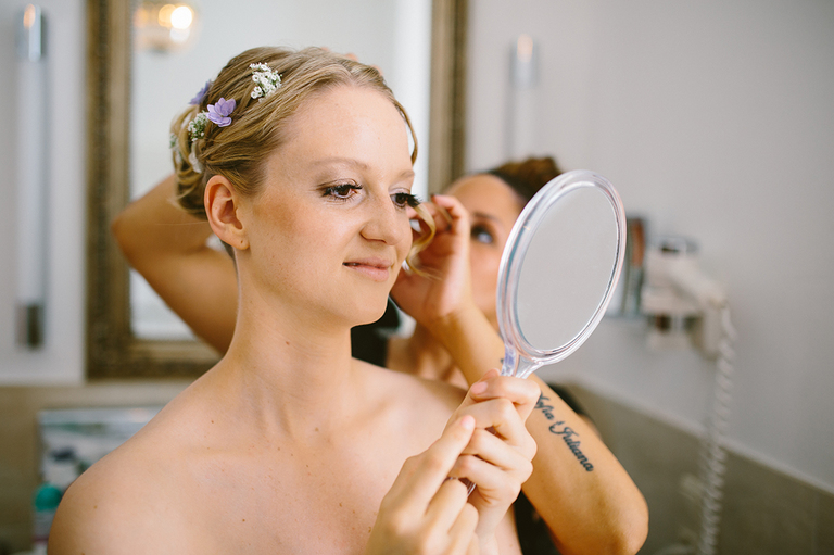Braut schaut in den Spiegel auf die Haare