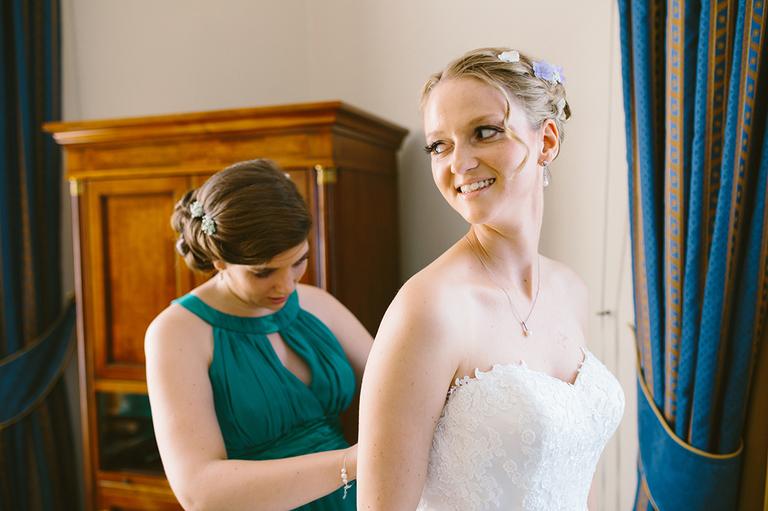 Braut wird von Trauzeugin angezogen