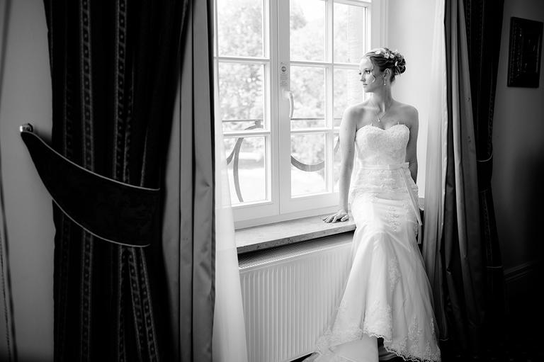Braut sitzt auf dem Fensterbrett und schaut aus dem Fenster