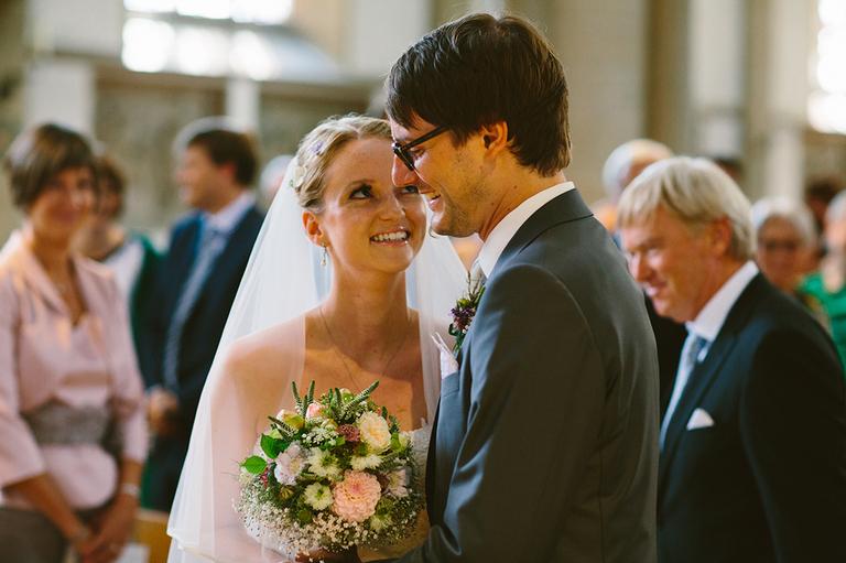 Braut und Bräutigam schauen sich in der Kirche verliebt an