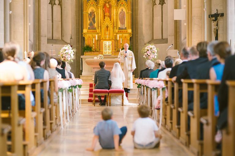 Kinder schauen sich die Trauung eines Brautpaares in der Kirche an