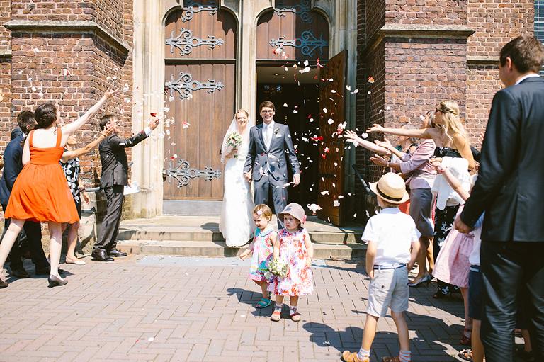 Braut und Bräutigam kommen aus der Kirche und werden mit Blumen beworfen