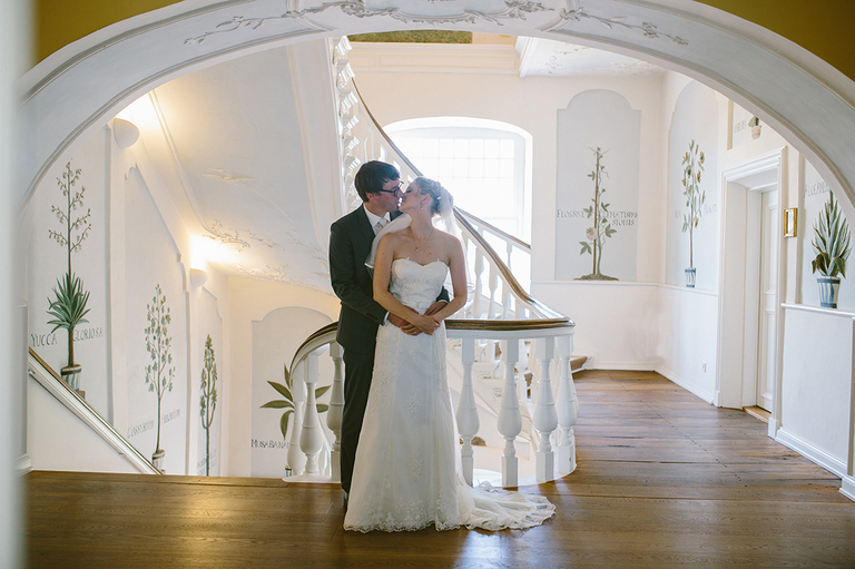 Brautpaar küsst sich unter einem Bogen