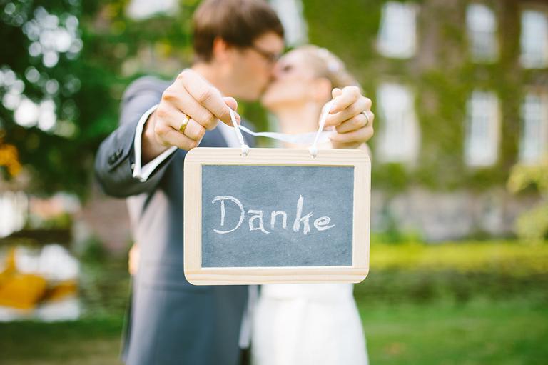 Brautpaar hält ein Schild in die Kamera