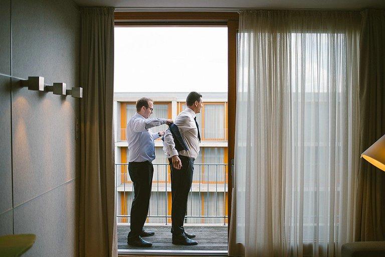 Trauzeuge hilft dem Bräutigam in das Sakko