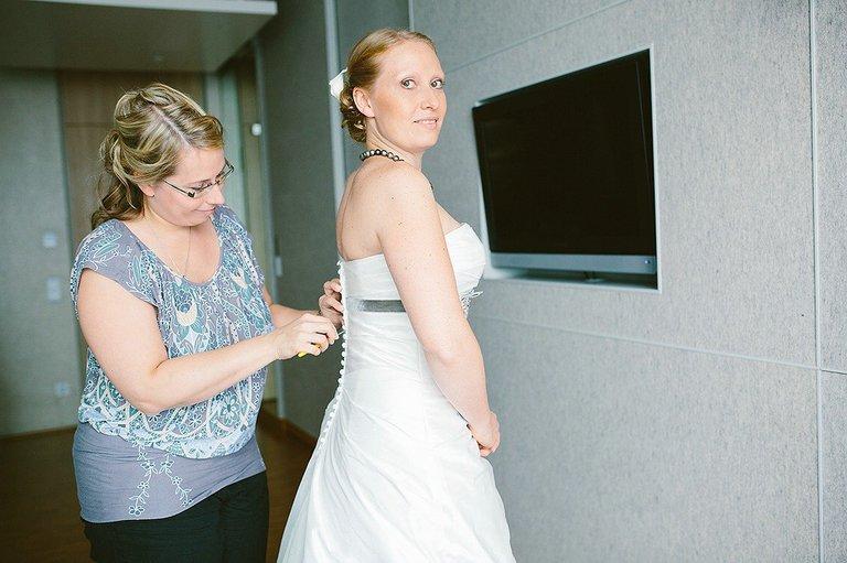 Schwester der Braut hilft der Braut in das Kleid