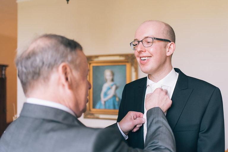 Vater vom Bräutigam bindet seinem Sohn die Krawatte