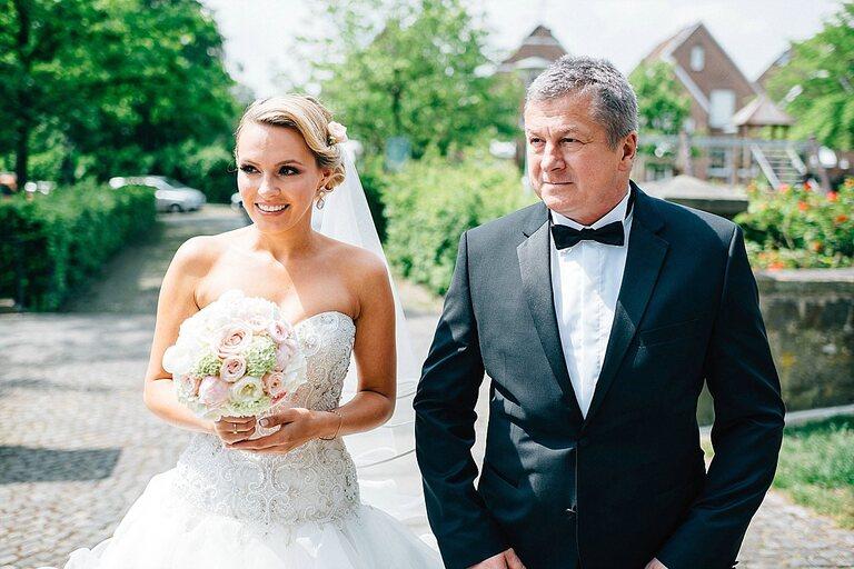 Braut mit ihrem Vater vor der Kirche