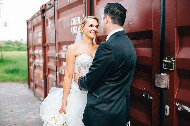 Braut und Bräutigam vor einem Überseecontainer