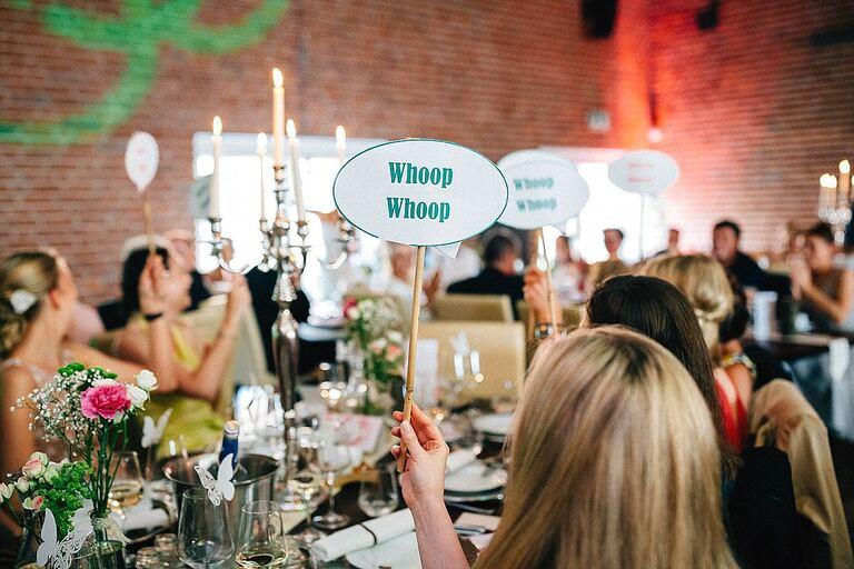 Hochzeitsgäste halten Schilder hoch