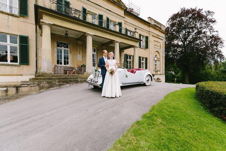Brautpaar mit dem Auto vor dem Schloss Harkotten ©Markus Koslowski Hochzeitsfotograf Warendorf