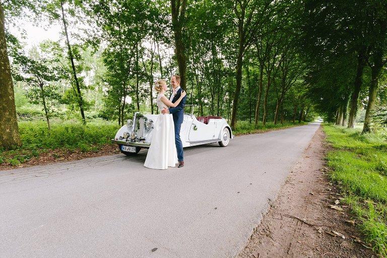 Brautpaar mit Auto in einer Allee in Warendorf ©Markus Koslowski Hochzeitsfotograf Warendorf