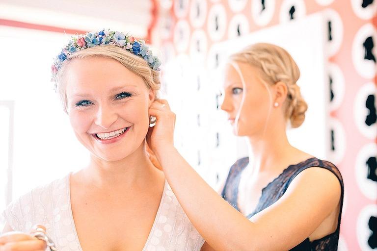 Braut bekommt von Ihrer Trauzeugin Ohrringe angelegt