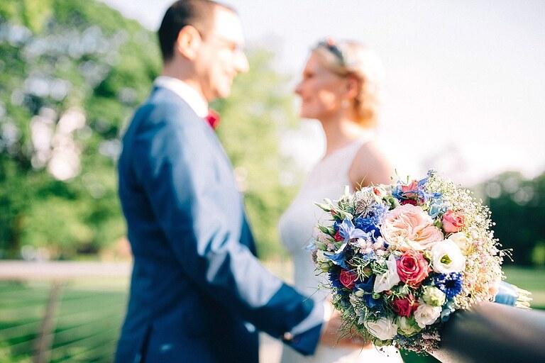 Brautstrauß und Brautpaar im Hintergrund