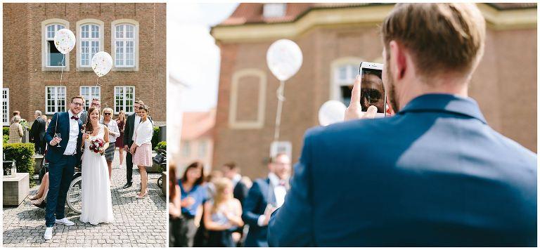 Gast macht ein Bild mit dem Smartphone von dem Brautpaar - Hochzeitsfotograf Lotharinger Kloster